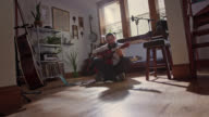 WS SLO MO. Young artist sings and plays guitar on living room floor of modern apartment studio.