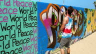 Young artist spraying and painting graffiti on the wall in Venice Beach, Los Angeles, California, 4K