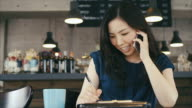 Young Asian Business Woman Talking over Phone and Writing