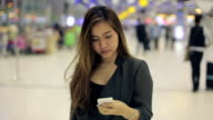 Young asian business woman using mobile phone at airport
