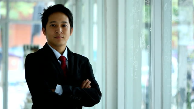 Young Asian businessman stands