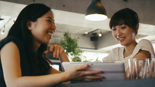 Young asian cafe owner using tablet and teaching