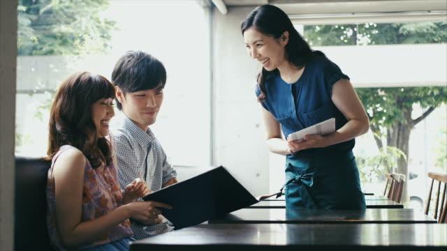 Junge asiatische paar Bestellung in einem Café