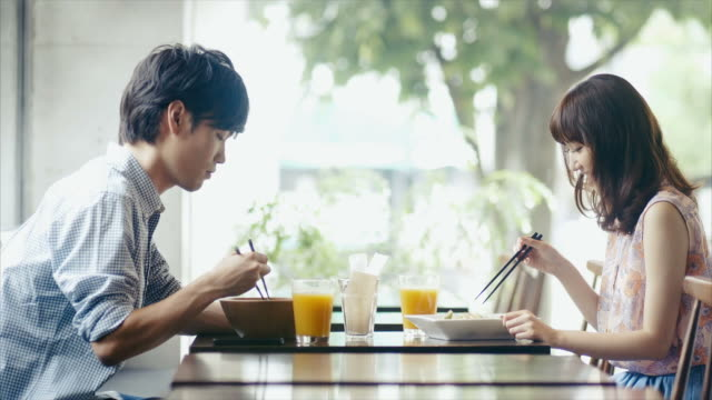 Young Asian Couple Tasting Food with Chopsticks in a Restaurant