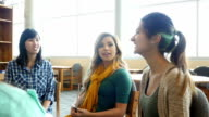 Young Asian female teacher leads a study or support group in library at STEM school