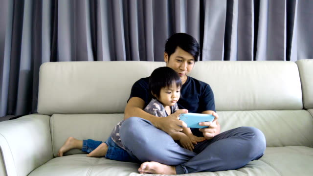 4K Young Asian man playing games on smartphone with baby boy.
