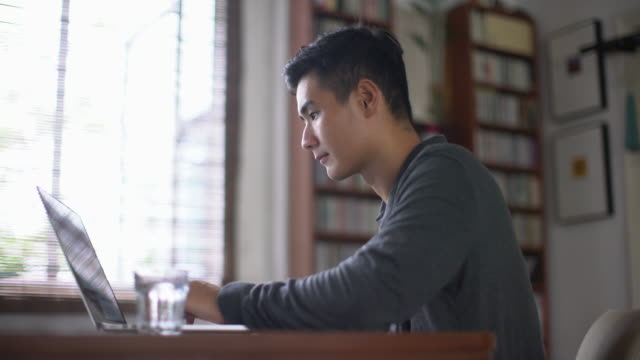 MS young Asian man working on a laptop at home.