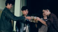 Young asian toasting beer bottles at party, slow motion