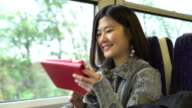 Young Asian woman digital tablet on a train.