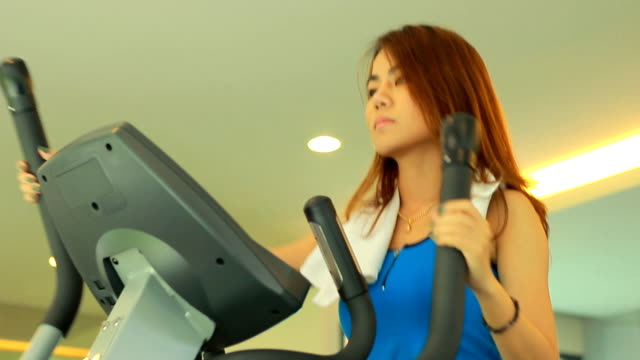 Young asian woman exercising at a modern gym