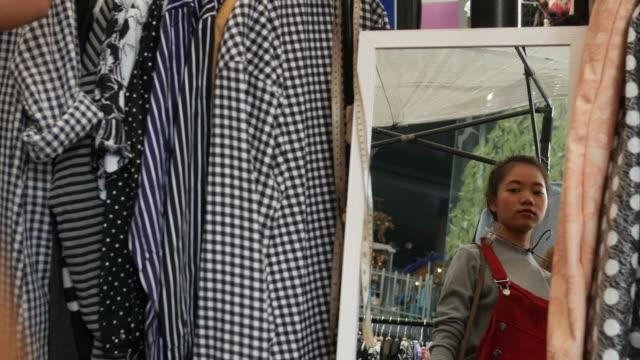 ung asiatisk kvinna passande klänning i boutique