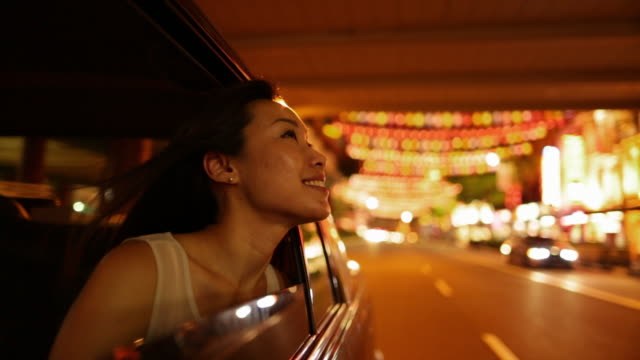 TS Young Asian woman looking at Chinese lanterns out of car window at night.