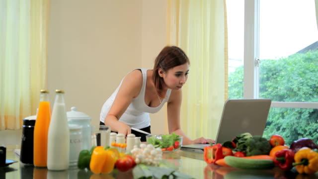 Junge asiatische Frau, die auf der Suche nach einem Rezept