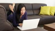 Junge asiatische Frau liegt auf dem Sofa mit laptop