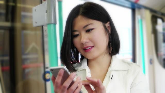 Jonge Aziatische vrouw op een trein met haar GSM.