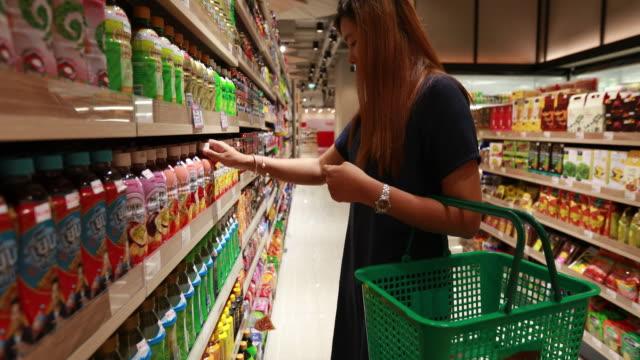 Junge asiatische Frau im Supermarkt einkaufen.
