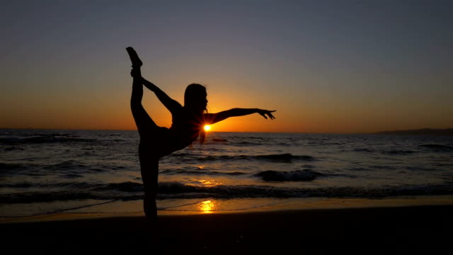 Young Asian woman stretching during yoga pose on beach at sunset