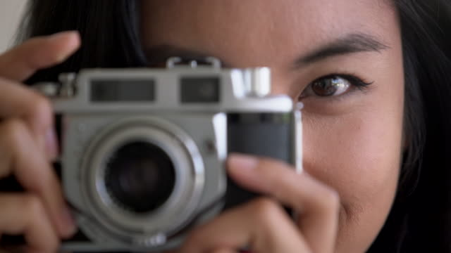 ECU Young Asian woman taking a photo with a vintage camera