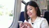 Giovane asiatica donna messaggi di testo su un treno.