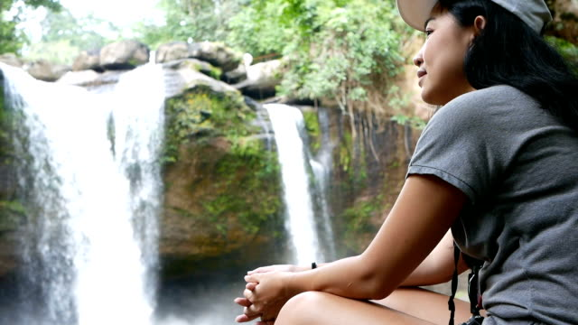 Young Asian woman traveler sitting in front of waterfall