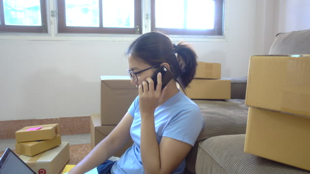 Unga asiatiska kvinnor kontrollera inkorg och använda telefon för att få order från kunden