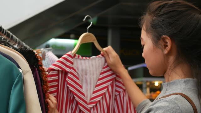 Unga asiatiska kvinnor shopping på gatan marknaden