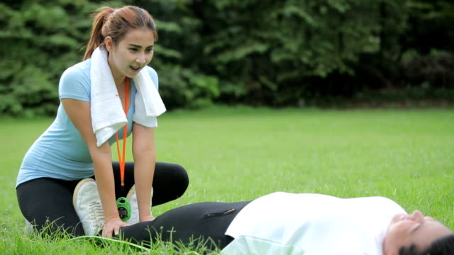 Young asian women with personal trainer doing exercises
