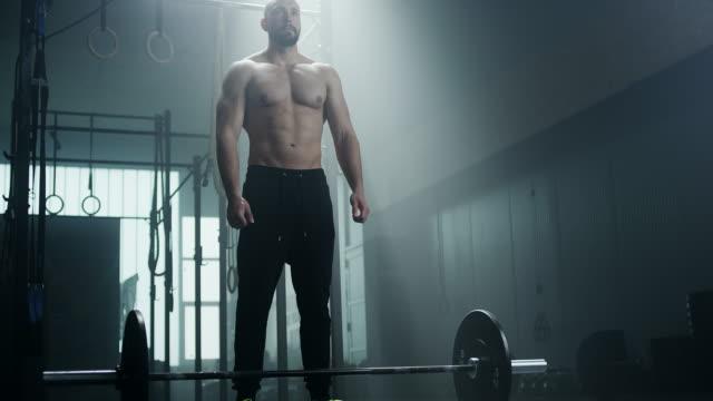 Junge Sportler Mann Übung mit Gewichten im Fitnessstudio