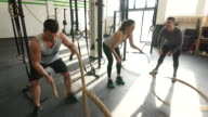 Young athletes doing gym battle rope exercises