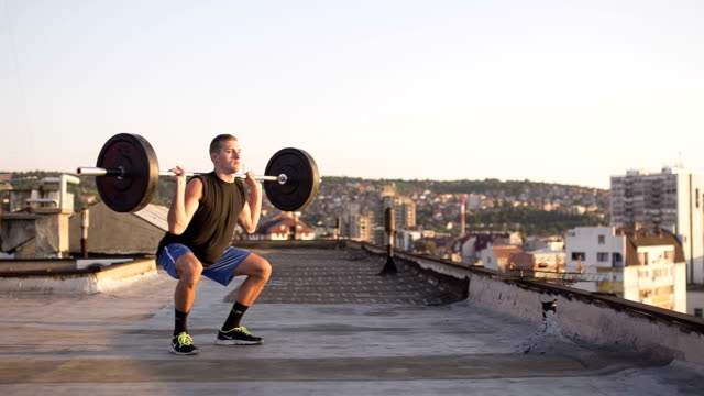 Young Athletic Man Doing Weighted Squat