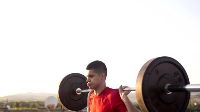 Junge sportliche Mann, Die gewichtete Squat