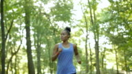 Young athletic woman running off road comes into view and rests, checking her watch