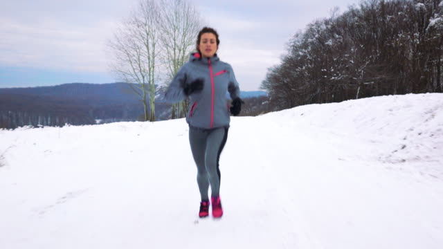 Young athletic woman running on a snow during cold winter day.
