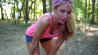 Young athletic woman stretching muscles before running in park
