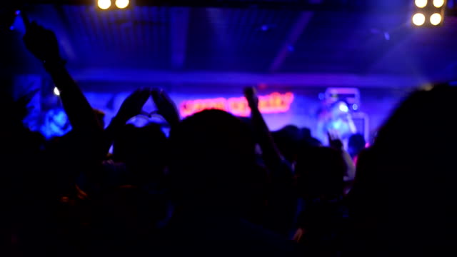 Young Audience waving hands on concert in nightclub