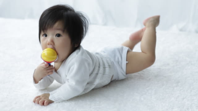 MS Young baby laying down, playing with baby rattle/Singapore