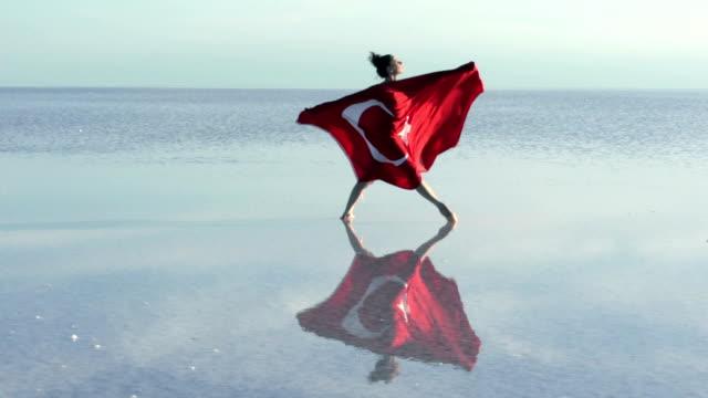Jungen Ballerina auf dem Wasser mit türkischer Flagge