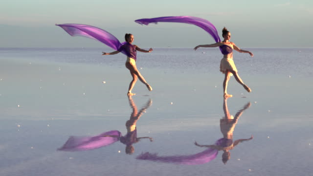 Young ballerinas dancing on the salt lake with color tulle