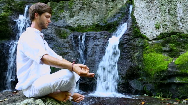 Young bearded man doing meditation near a waterfall