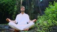 Young bearded man doing yoga meditation near waterfall