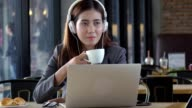 Young beautiful asian businesswoman listening music and drink coffee in cafe.