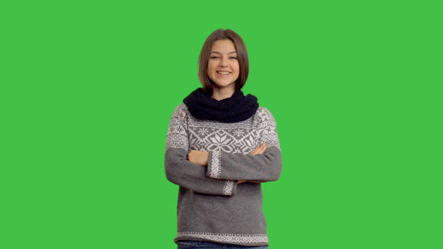 young beautiful woman in a winter sweater on a green background