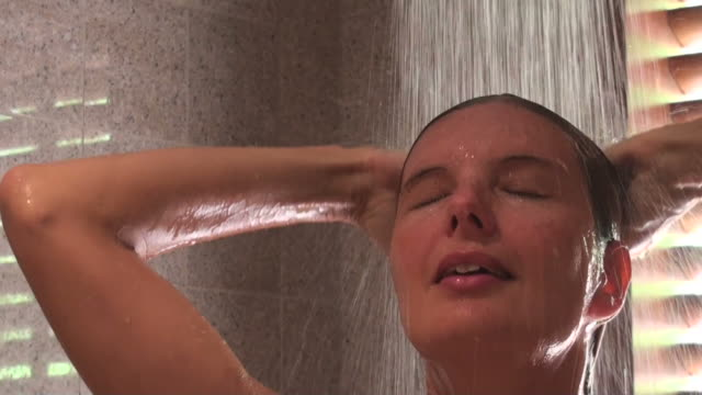 Young beautiful woman relaxing while taking her shower