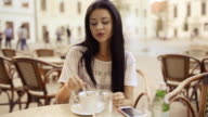 Young beauty woman waiting and drinking coffee at patio.