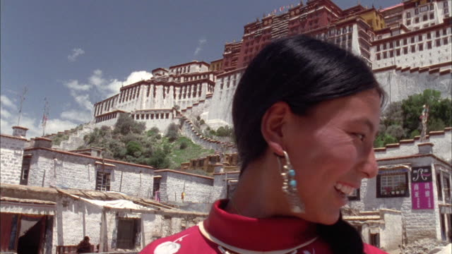 Young Bhutanese woman smiles at camera with mountain palace in background Available in HD.
