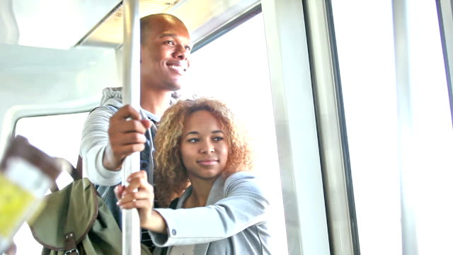Young black couple riding train, looking out window