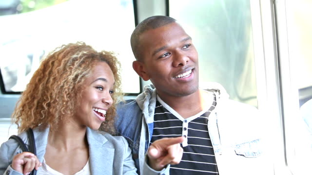Young black couple riding train, talking, looking at view