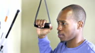Young black man doing physical therapy on arm or shoulder