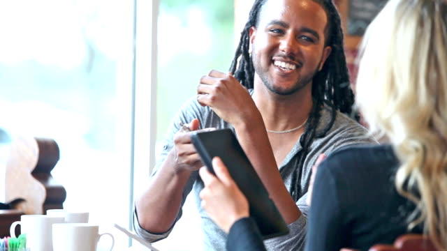 Young black man in coffee shop talking with woman