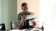 Young black man paying bills